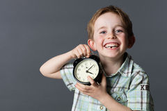 Laughing little kid with missing tooth holding clock for time. Laughing little kid with freckles and missing tooth holding a clock for time concept and youth stock image