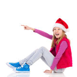 Laughing Little Santa Girl Pointing Royalty Free Stock Photography