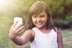 Laughing  llittle girl is doing selfie outdoors. Royalty Free Stock Photo