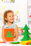 Laughing looking girl holds card with Xmas tree Royalty Free Stock Images