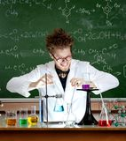Laughing mad professor combines some liquids. In his laboratory Stock Photography