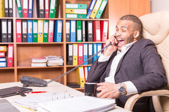 Laughing main talking on phone in office Stock Images