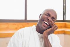 Laughing man in bathrobe talking on phone Royalty Free Stock Photos