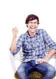 Laughing man on chair. Young hispanic man wearing glasses, blue shirt with rolled up sleeves and jeans sitting on chair with hand near his face and loudly stock photo