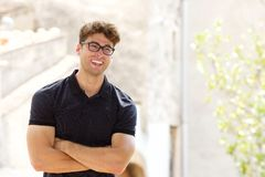Laughing man with glasses standing with arms crossed Royalty Free Stock Photography