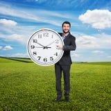 Laughing man holding big white clock Royalty Free Stock Photos