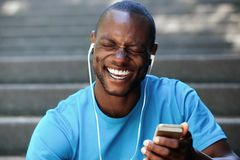 Laughing man holding cell phone listening with earphones. Laughing black man holding cell phone listening with earphones Stock Photography