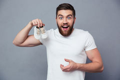 Laughing man holding small shoe Royalty Free Stock Photography