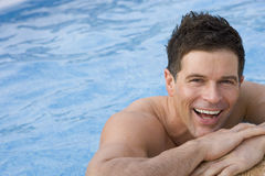 Laughing man leaning on edge of swimming pool stock images