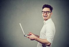 Laughing man with modern laptop stock images