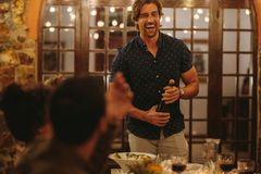 Laughing man opening champagne at party royalty free stock images
