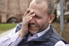 Laughing man. Outdoor shot of laughing man sitting on a park bench Royalty Free Stock Images