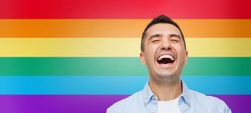 Laughing man over rainbow flag stripes background. Gay pride, homosexual, emotions and people concept - laughing man over rainbow flag stripes background royalty free stock images