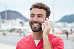 Laughing man with red shirt at cellphone in the city Stock Photos