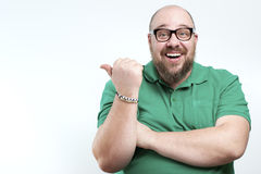 Laughing man shows his finger to the side. Royalty Free Stock Photo