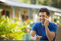 Laughing Man Sitting Outdoors Stock Photo