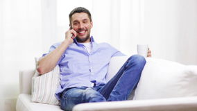 Laughing man with smartphone at home stock video footage