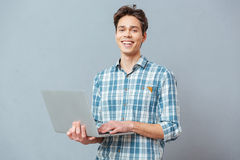 Laughing man standing with laptop computer Stock Photography