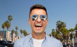 Laughing man in sunglasses over venice beach stock photography