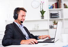 Laughing man talking on headset at office. Laughing man talking on headset at company office Royalty Free Stock Images