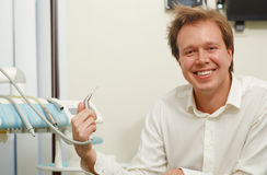 Laughing man with tousled hair holding dental tool Stock Photography