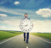 Laughing man walking on the road. And holding big white clock Stock Photography
