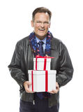 Laughing Man Wearing Black Leather Jacket Holding Christmas Gifts on Whit. Handsome Man Wearing Black Leather Jacket and Holiday Scarf Holding Christmas Gifts Stock Photography