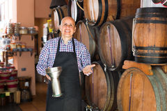 Laughing man wine maker taking wine from wood Stock Photography