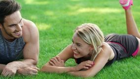 Laughing man and woman flirting in park. Sport couple lying on green grass. Laughing man and woman flirting in summer park. Sport couple lying on green grass stock footage