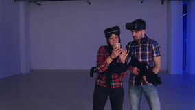 Laughing man and woman in virtual reality headsets looking at their funny photos on the phone. Professional shot in 4K resolution. 079. You can use it e.g. in stock video footage