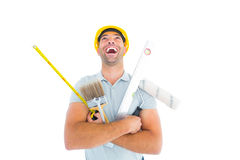 Laughing manual worker holding various tools Royalty Free Stock Image