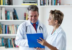 Laughing mature general practitioner with female doctor at work. At hospital royalty free stock image