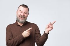 Laughing mature man with beard pointing finger aside stock photography
