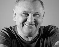 Laughing mature man closeup. Black and white portrait of cheerful aged man in t-shirt smiling with dimples Royalty Free Stock Photography