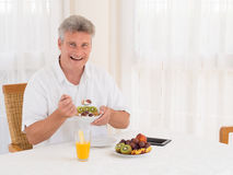 Laughing mature man eating a healthy cereal breakfast. Laughing attractive mature senior man full of vitality sitting at the table eating a healthy breakfast of Stock Image