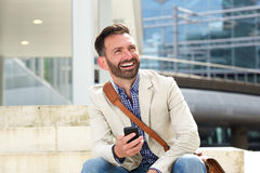 Laughing mature man sitting outdoors with cellphone Stock Photos