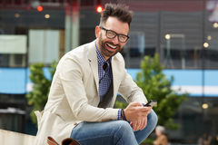 Laughing mature man sitting outdoors with mobile phone. Portrait of mature man sitting outdoors with mobile phone and laughing Stock Photos