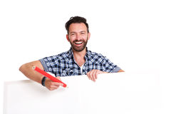 Laughing mature man writing over blank poster. Portrait of laughing mature man writing over blank poster against white background royalty free stock image