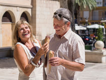 Laughing mature senior couple eating ice cream having fun. Laughing mature senior couple eating ice cream together while he try to steal her ice cone on a hot Stock Photos