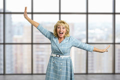 Laughing mature woman on office window background. Laughing white-skin woman stretching her arms diagonally. Cheerful elderly lady posing with stretching hands Stock Photos
