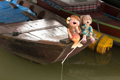 Laughing Mermaids. Two junior mermaids catching fishes on a boat, are having fun perhaps because of sneaking away from home Royalty Free Stock Photo
