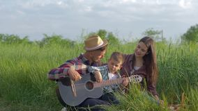 Laughing merry man teaches kid boy to play guitar while mom is enjoying and smiling while relaxing on family picnic in. Nature in green field close-up stock footage