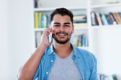 Laughing mexican hipster man with beard at phone royalty free stock photos