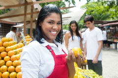 Laughing mexican saleswoman with customers on a farmers market. With client and fruits in the background stock images