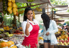 Laughing mexican saleswoman showing thumb on a farmers market. With client and fruits in the background stock image