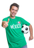 Laughing mexican soccer fan with ball showing thumb. Football fan from Mexico in a green jersey with ball laughing at camera and showing his thumb on a isolated Royalty Free Stock Image