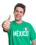Laughing mexican sports fan showing thumb up. Football fan from Mexico in a green jersey laughing at camera and showing his thumb up on a isolated white Royalty Free Stock Photo