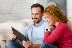 Laughing middle aged couple using tablet at home Stock Photos