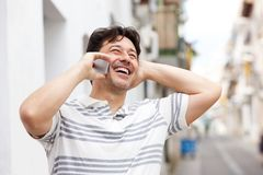 Laughing middle aged man talking on smart phone. Close up portrait of laughing middle aged man talking on smart phone Royalty Free Stock Photos