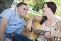 Laughing Mixed Race Couple at the Park Playing Guitar and Singing Royalty Free Stock Photos
